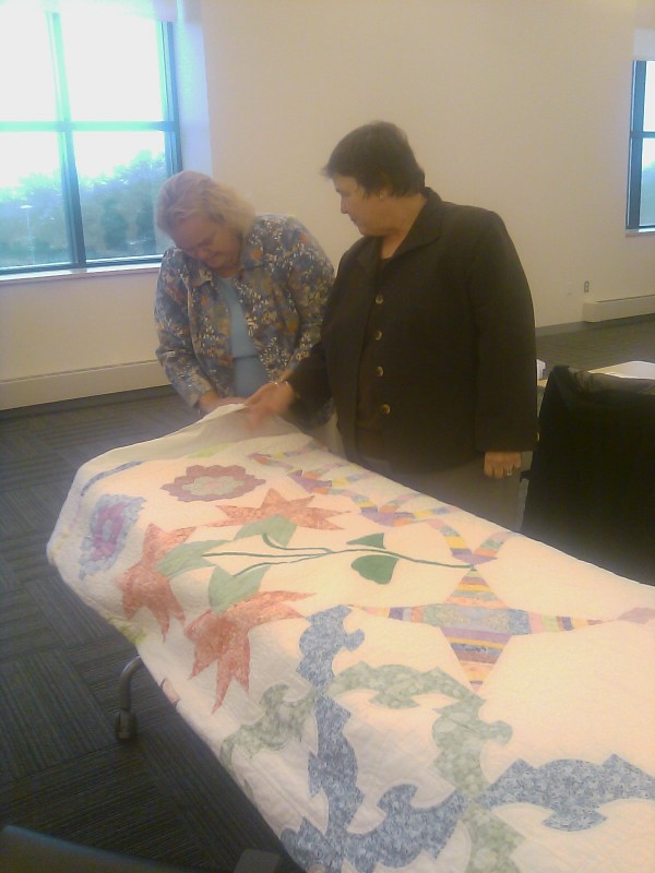 Bangor lawyer Roberta Winchell (right) shows Lincoln lawyer Patricia Locke the quilt the family of an elderly client made for Winchell at the Penobscot Judicial Center on Monday where both lawyers received the Katahdin Council Award from the Maine Supreme Judicial Court.