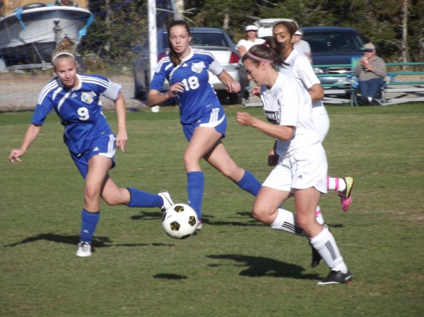 Emma LeGallais advances the ball for the University of Maine-Machias as two UM-Presque Isle players scramble to defend Friday in Machias. LeGallais scored three goals in her team's 6-2 win.