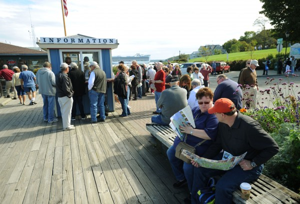 Tourists and cruise ship passengers jam the streets and information booth at the Bar Harbor town pier after most of the scheduled bus tours of Acadia National Park were canceled because of the federal government shutdown on Tuesday.
