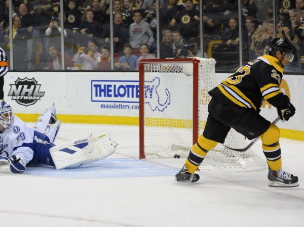 Boston Bruins center Chris Kelly scores a goal on a penalty shot past Tampa Bay Lightning goalie Anders Lindback during the first period at TD Banknorth Garden in Boston Thursday night.