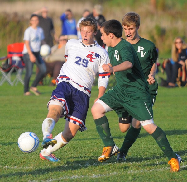 Bangor Christian's Jay Bishop (left) and Penobscot Valley's Darren Clement battle for the ball during the first half of the game in Bangor Thursday. On the right is Penobscot Valley's Porter McLaughlin.