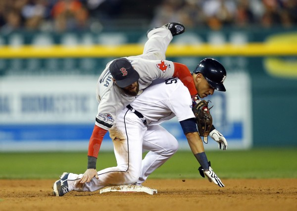 Boston Red Sox second baseman Dustin Pedroia (left) collides with Detroit Tigers shortstop Jose Iglesias (1) as he turns a double play during the sixth inning in game four of the American League Championship Series baseball game at Comerica Park in Detroit. The Tigers won 7-3 to even the series at 2-2.