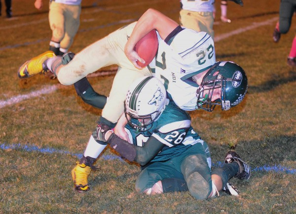 Mount Desert Island High School's Teagan Candage (top) is tackled by Old Town High School's Tyler Wengrzynck during the first half of the game in Old Town Friday evening.