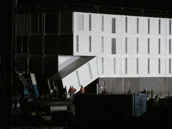 Workers at Cianbro's Rickers Wharf Marine Facility in Portland on Thursday night inspect what appears to be a ramped entrance into a box-like four-story structure delivered there by barge. Cianbro CEO Peter Vigue said he cannot divulge what the structure is or who hired his company to work on it.