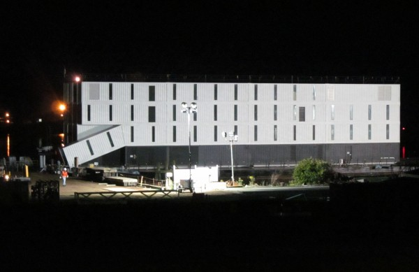 A mysterious four-story structure is docked on a barge at Cianbro's Rickers Wharf Marine Facility on the West End of Portland Thursday night. The structure was shipped to Portland from Connecticut, where it was shrouded in secrecy and the focus of intense speculation.