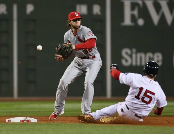 St. Louis Cardinals shortstop Pete Kozma loses the ball as he transfers from his glove to his throwing hand as Dustin Pedroia (15) of the Boston Red Sox slides in the first inning in Game One of the World Series at Fenway Park in on Wednesday.