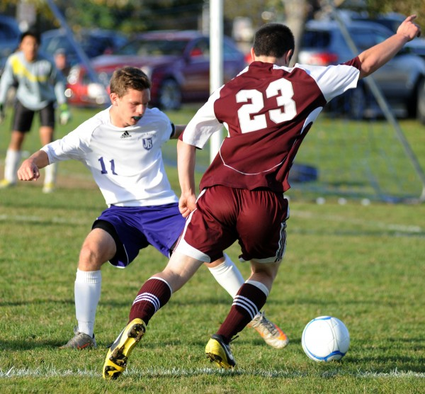 John Bapst's Kyle Dube tries to block Ellworth's Jake Jordan as he goes for a goal in Thursday afternoon's game against John Bapst.