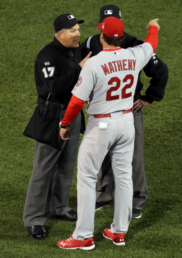 St. Louis Cardinals manager Mike Matheny argues with crew chief John Hirschbeck as umpires reversed a call that originally had ruled Dustin Pedroia of the Boston Red Sox out at second base after a fielding error by shortstop Pete Kozma in the first inning in Game One of the World Series at Fenway Park on Wednesday.