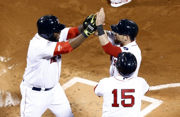 Boston Red Sox second baseman Dustin Pedroia (15) and center fielder Jacoby Ellsbury (2) celebrate as Boston Red Sox designated hitter David Ortiz (left) celebrate during the first inning during Game One of the World Series at Fenway Park on Wednesday.