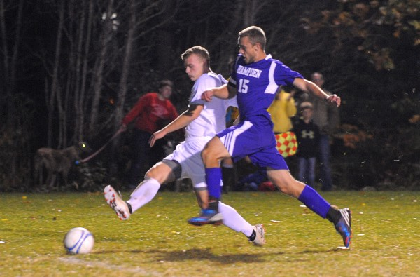 Bangor High School's Nate Bach (left) and Hampden Academy's Cameron Scott vie for the ball during the game in Bangor Tuesday evening.