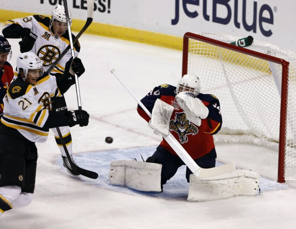 Florida Panthers goalie Tim Thomas (34) blocks a shot as Boston Bruins left wing Loui Eriksson (21) and right wing Reilly Smith (18) look for the deflection in the first period at BB&T Center Thursday night in Sunrise, Fla.