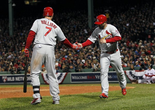 St. Louis Cardinals shortstop Daniel Descalso (33) celebrates with left fielder Matt Holliday (7) after scoring against the Boston Red Sox during the seventh inning of game two of the World Series at Fenway Park in Boston Thursday night. The Cardinals won 4-2.