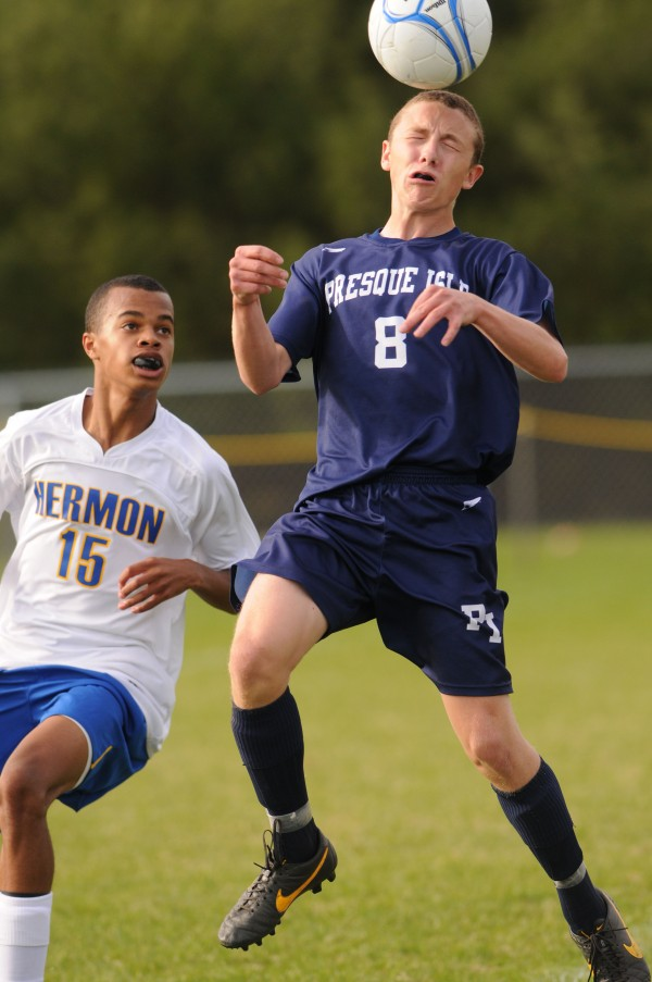 Hermon's Isaiah Marseille watches as Presque Isle's Alex Michaud heads the ball during first half action at Hermon on Monday.