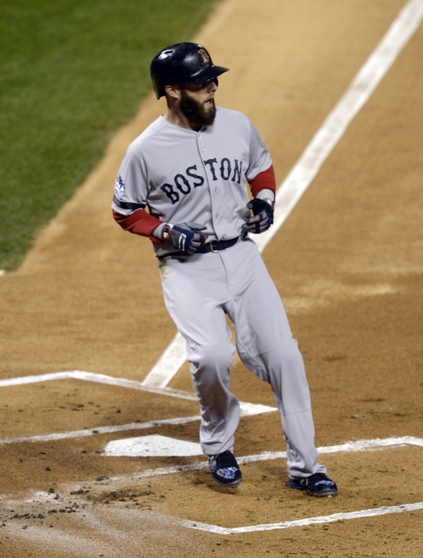 Boston Red Sox second baseman Dustin Pedroia scores a run against the St. Louis Cardinals in the first inning during game five of the World Series at Busch Stadium.