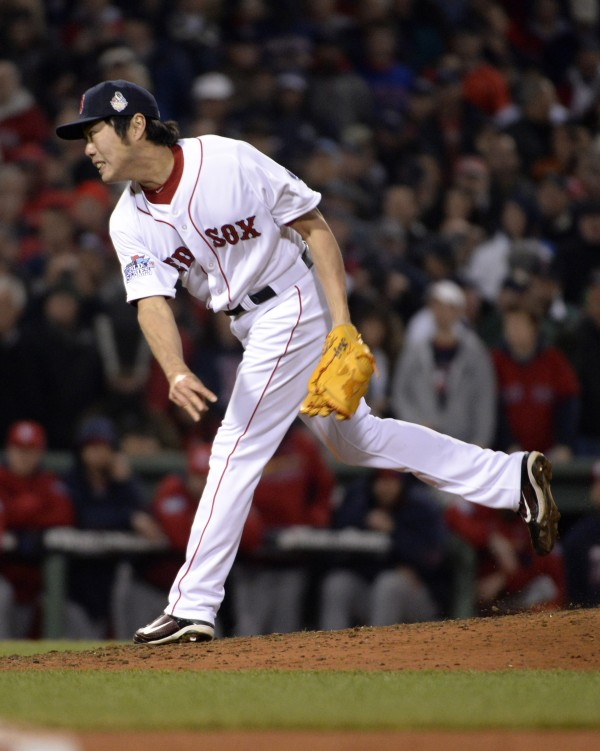 Boston Red Sox relief pitcher Koji Uehara throws a pitch against the St. Louis Cardinals in the 9th inning during game six of the MLB baseball World Series at Fenway Park.
