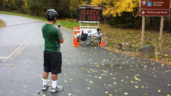 Vic Suzuki of Loz Angeles takes a photo of an electronic sign in Acadia National Park on Thursday. Suzuki, who is biking from Fort Kent to Boston, said he is glad the national park reopened as he was passing through. &quotI came at the right time,&quot he said.