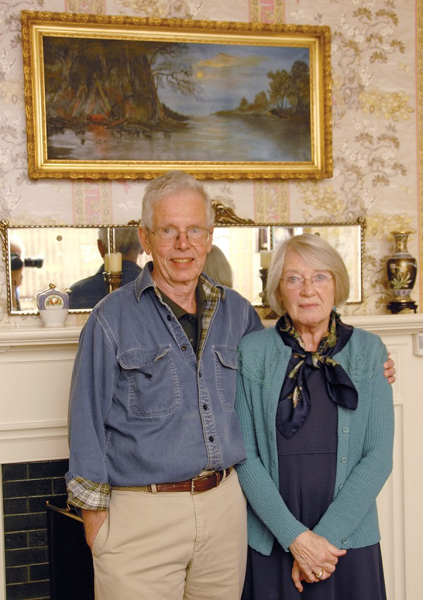 Dr. Alan Boone and his wife, Gayle, stand beneath an oil painting done by Gayle's grandmother, Zeula Miller Carson. The Boones recently had another oil painting in their home restored by John Squadra, a fine art restorer.