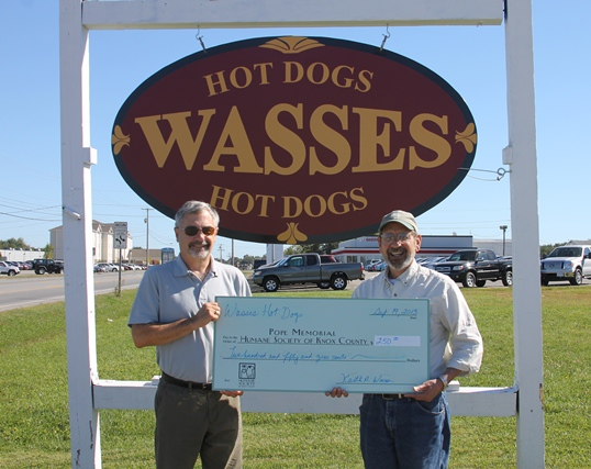 Wasses Hot Dogs owner Keith Wass (left) presents proceeds check from their 'Eat a Dog, Save a Cat' promotion to PMHSKC Board President Richard Procopio