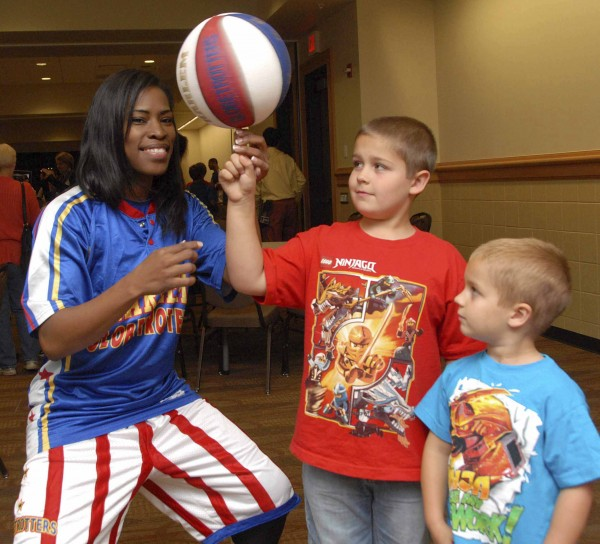 BANGOR, MAINE - Friday, Sept. 20, 2013 - Four-year-old Reed Johnson (right) of Bangor watches as Harlem Globetrotter Tammy &quotTNT Brawner balances a rotating basketball on the right forefinger of 8-year-old Roman Johnson. The Johnson brothers met four Globetrotters prior to Friday night's game at the Cross Insurance Center after their parents entered a contest sponsored by the Bangor Daily News.