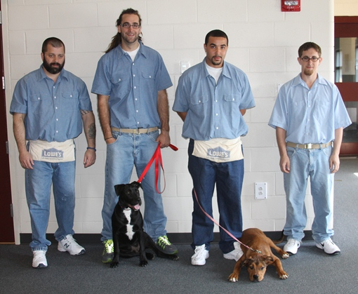 Maine State Prison K9 Program trainers with graduating PMHSKC dogs 'Chip' (left) and 'Bandit' (right)