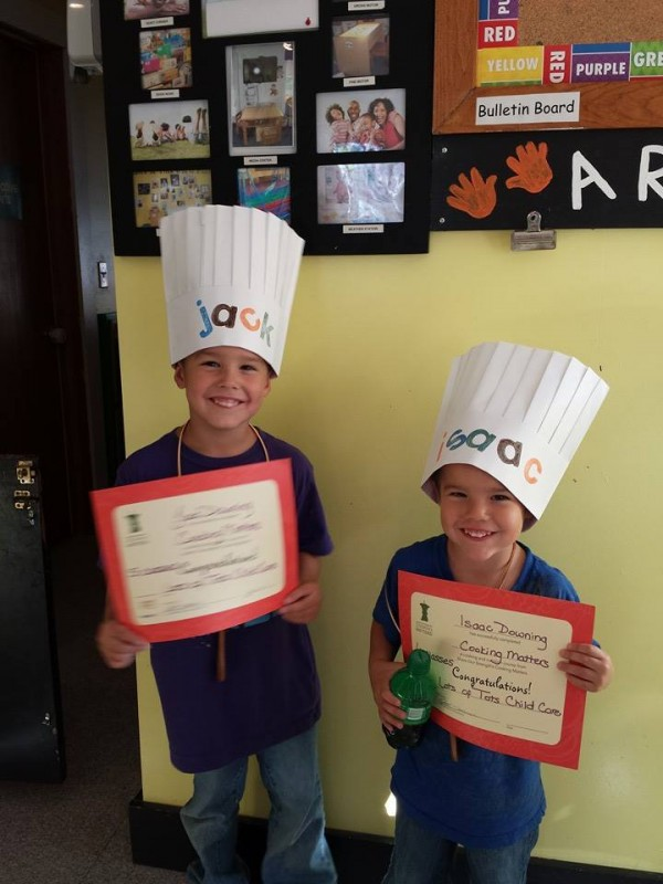 Jack and Isaac are all smiles as they sport their new chefs hats and Cooking Matters graduation certificates.