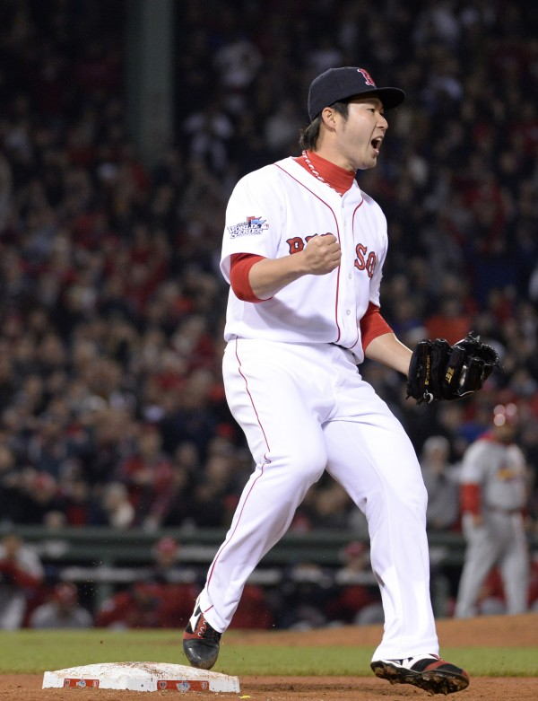 Boston Red Sox relief pitcher Junichi Tazawa reacts after forcing out St. Louis Cardinals designated hitter Allen Craig (not pictured) to end the top of the 7th inning during game six of the World Series at Fenway Park.