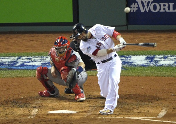 Boston Red Sox right fielder Shane Victorino hits a three-run double against the St. Louis Cardinals in the third inning during game six of the MLB baseball World Series at Fenway Park.