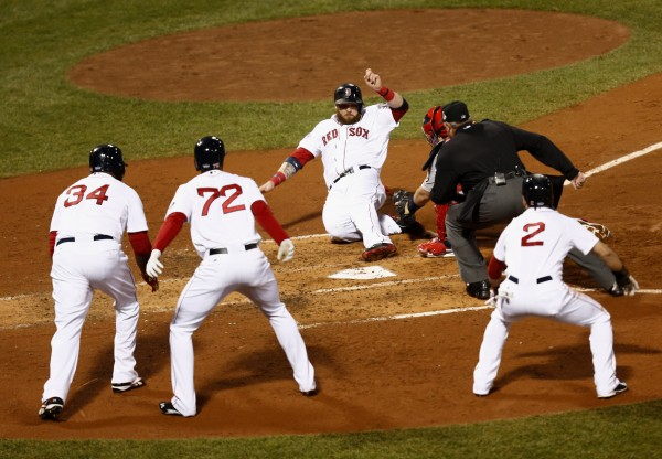 Boston Red Sox left fielder Jonny Gomes (5) slides in safely against St. Louis Cardinals catcher Yadier Molina (4) as designated hitter David Ortiz (34), third baseman Xander Bogaerts (72), and center fielder Jacoby Ellsbury (2) look on during the third inning of game six of the World Series at Fenway Park.