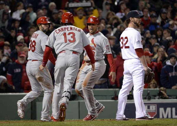 Boston Red Sox relief pitcher Craig Breslow (32) reacts as St. Louis Cardinals second baseman Matt Carpenter (13) celebrates with his teammates Pete Kozma (38) and Jon Jay (19) after scoring a run in the 7th inning during game two of the World Series at Fenway Park.