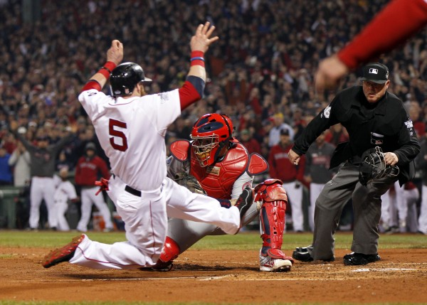 Boston Red Sox left fielder Jonny Gomes (5) slides in safely against St. Louis Cardinals catcher Yadier Molina (4) on a 3-RBI double by Boston Red Sox right fielder Shane Victorino (not pictured) during the third inning of game six of the World Series at Fenway Park.