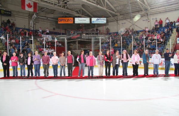 Prior to the game, breast cancer survivors were honored in an on-ice ceremony. Carlene Sperry of Auburn, Kelly Ripley of Belmont, Kay Langlin of Turner, Sue Levasseur of Lewiston, Karen Albert of New Gloucester, Dottie Timberlake of Topsham, Kathy Stevens of Brunswick, Tia Adams of Bath, Monique Sullivan of Auburn, Robin Goodwin of Westbrook, Rayleen Lima of Oxford, Linda Knowles of Harpswell, Jane Audette of Auburn, Michelle Abbott of Oxford, Kim Turner of Livermore, Dina Ingraham of Biddeford, Jean Libbey of Auburn, Sheila Barnies of Lewiston, Alan Stone of Raymond, and Darlene Molboski of Bath (left to right in photo) were each presented with flowers by the Pirates players prior to the ceremonial puck drop.