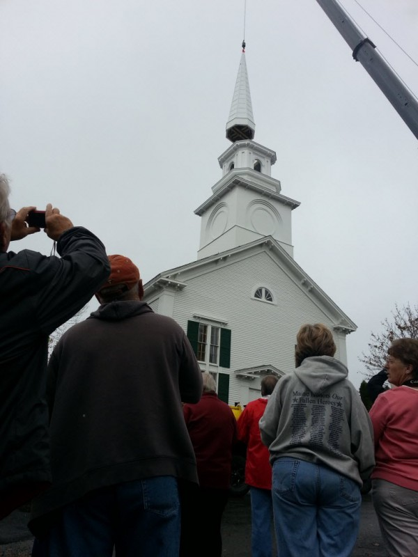 Onlookers watch as the new steeple for the Stockton Springs Community Church was gently lifted into place Friday morning, the culmination of six years of fundraising by the a committee comprised of women between 72 and 91 years of age.