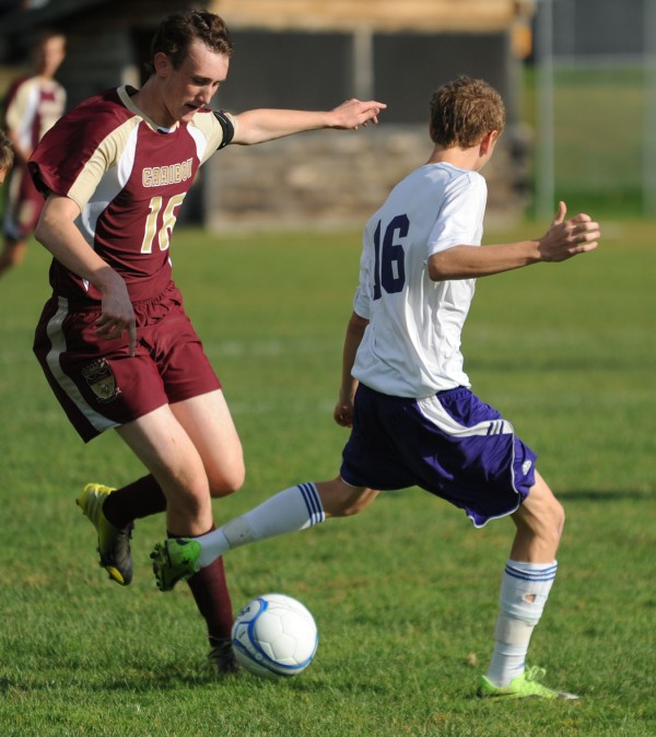 Caribou's Cody Hebert and John Bapst's Alex Mooney battle for control of the ball during first half action on Tuesday at Bangor.