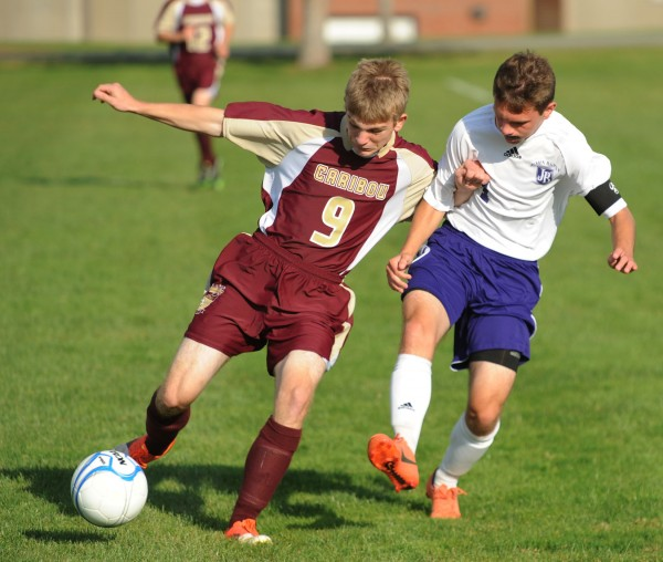Caribou's Hunter Milliard  and John Bapst's Kyle Dube battle for control of the ball during first half action on Tuesday at Bangor.