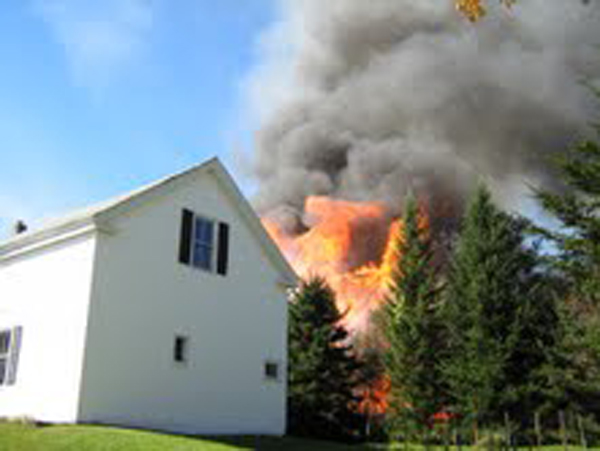 A three-story garage engulfed in flames burned Sunday afternoon, threatening nearby structures including the parsonage of the First Baptist Church of Blue Hill.