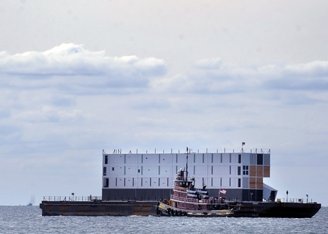 The tugboat Rowan W. McAllister leads the &quotmystery building&quot on its barge down the Thames River bound for Long Island Sound from the Admiral Harold E. Shear State Pier in New London Wednesday, Oct. 9, 2013.