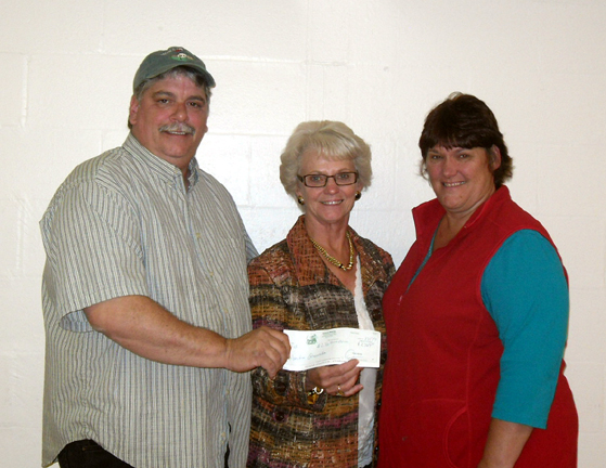 Ryan Poirier, Spectrum Generations Regional Nutrition Coordinator, (left) is presented with a check by (right) Rita Sukeforth and Annette Marin from their Sukeforth Annual Bing-Sol Pig Roast & Auction.