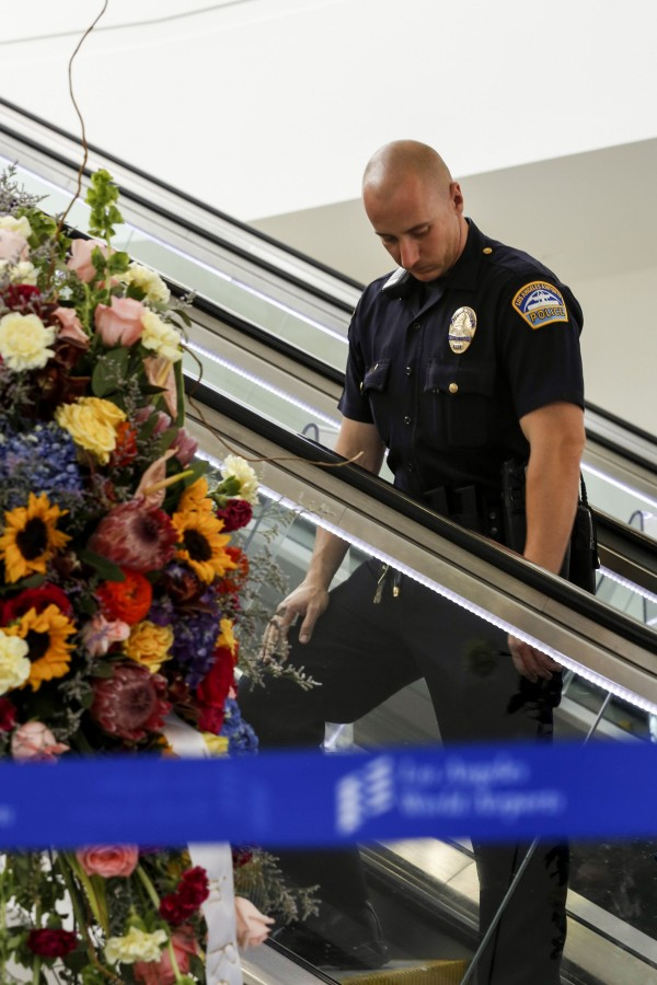 An Los Angeles Airport Police officer passes by a flower memorial in terminal three for slain TSA officer Gerardo Hernandez at LAX on November 3, 2013, in Los Angeles, California.