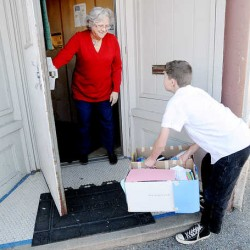 Beverley Robbins opens the door at Hope Haven Gospel Mission in Lewiston as Patrick Myers, 11, delivers donated socks to the homeless shelter Monday. The fifth-grader organized a sock drive at Park Avenue Elementary School in Auburn to help the homeless.