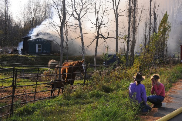 Homeowner Raydell Henderson, left, and his daughter Katelynn Henderson watch helplessly as their home on Sawyer Road in Levant burns on Oct. 21.
