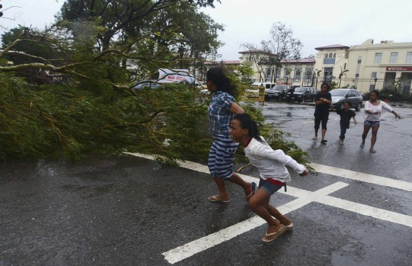 Residents rush to safety past a fallen tree during strong winds brought by Typhoon Haiyan that hit Cebu city, central Philippines Nov. 8, 2013.