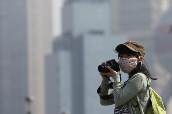 A tourist wears a mask while taking pictures on the Bund in Shanghai during a hazy day November 8, 2013. Chinese cities should close schools, cut working hours and stop outdoor activities during the most severe spells of air pollution, the Ministry of Environmental Protection said earlier this month.