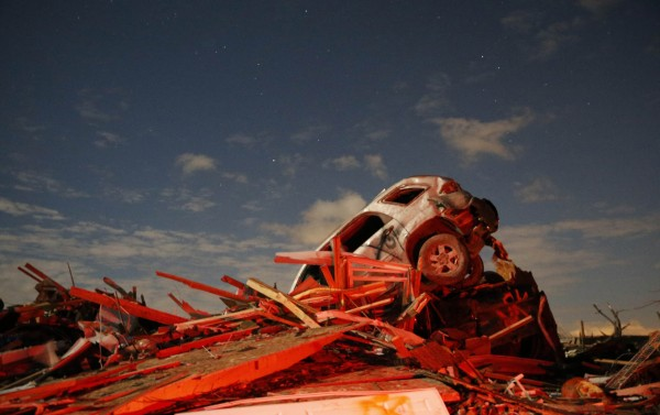 A vehicle sits on a pile of debris from the destruction caused by a tornado that touched down in Washington, Illinois, November 17, 2013. A fast-moving storm system triggered multiple tornadoes on Sunday, killing at least five people, injuring about 40 and flattening large parts of the city of Washington, Illinois as it tore across the Midwest, officials said.