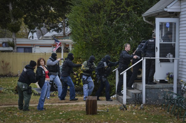 Members of the Manassas/Manassas Park/Prince William Narcotics Task Force arrest Terri Hilbrand, second from left, on Nov. 12, 2013 at her Manassas Park, Va. home. She is accused of distributing prescription pills illegally.
