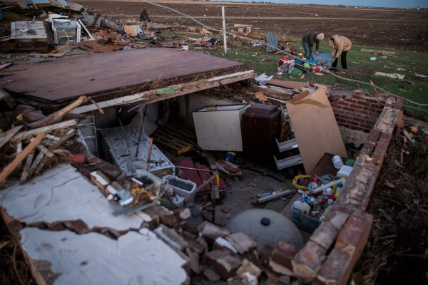 Ben Dubois, left, and his father Mark look over the remains of Ben's home on Main Street in Washington, Ill., after a tornado left a trail of damage on Sunday, Nov. 17, 2013.