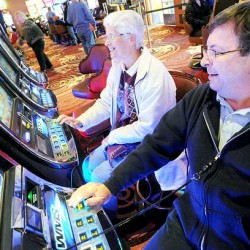 Chris Dispenzieri of Bangor and Greg Hudak of Brewer play the slot machines at the Oxford Casino on Thanksgiving Day.