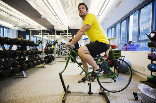 An employee demonstrates the use of an exercise cycle that powers a blender making a fruit smoothie inside the employee gym at the Google office in Toronto, November 13, 2012.