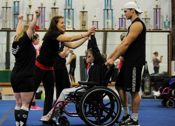 Instructor Brittany Madden (left) helps student Dawn Nicholson in practice on Oct. 17 at Big 10 Cheer in Hermon. Brittany and her husband, Josh Madden (right), who own Big 10 Cheer, started the Cheer Magic All Star special needs team in May.