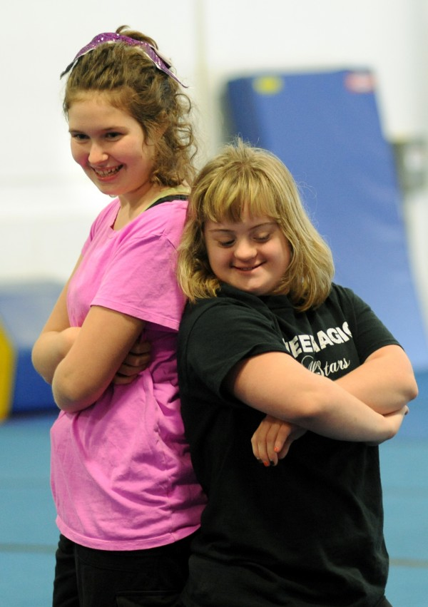 Sydney Newcomb (left) and Ciarra Boucher end a routine during practice on Oct. 17 at Big 10 Cheer where they are on the Cheer Magic All Star Special Needs Team. Newcomb and Boucher were the first two students in the class that began in May.