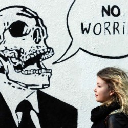 A woman walks past graffiti in the Temple Bar area of Dublin November 7, 2013. Ireland's international lenders confirmed on Thursday it had passed the final review of its 85 billion euro bailout, paving the way for it to become the first euro zone country to complete such a program.